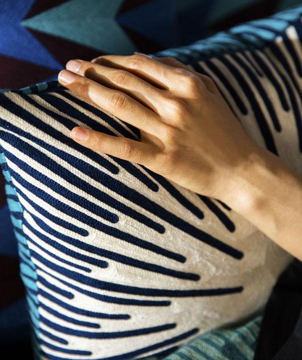 Une main de femme est posée sur unccoussin blanc avec des rayures bleu sombres.
